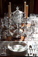 Detail of polished glassware and silver candlesticks on a dining table