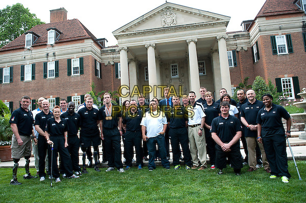 Prince Harry poses with a group of U.S. and British wounded warriors during a reception at the British Ambassador's Residence in Washington, D.C.,  USA..May 7th, 2012.royal royalty full length blue suit red tie group shot.CAP/ADM/CNP/KD.©Kevin Dietsch/CNP/AdMedia/Capital Pictures