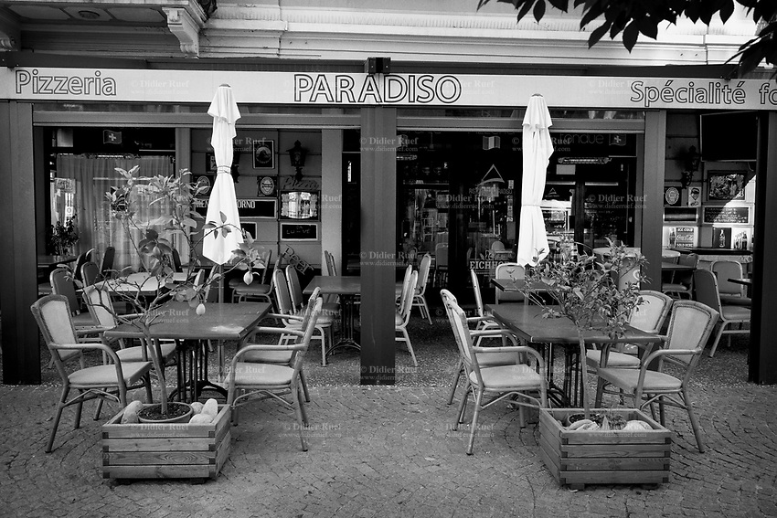 """Switzerland. Canton Ticino. Paradiso. Paradiso is a municipality in the district of Lugano. The restaurant Paradiso ( Paradise) is closed due the the Coronavirus (also called Covid-19). Tables and chairs on an empty  terrace. Two lemon trees. Due to the spread of the coronavirus, the Federal Council has categorised the situation in the country as """"extraordinary"""". It has issued a recommendation to all citizens to stay at home, especially the sick and the elderly. From March 16 the government ramped up its response to the widening pandemic, ordering the closure of bars, restaurants, sports facilities and cultural spaces. Only businesses providing essential goods to the population – such as grocery stores, bakeries and pharmacies – are to remain open. 22.04.2020 © 2020 Didier Ruef"""