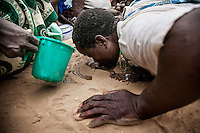 A witchdoctor drinks water from the ground to calm down a spirit during an initiation ceremony.