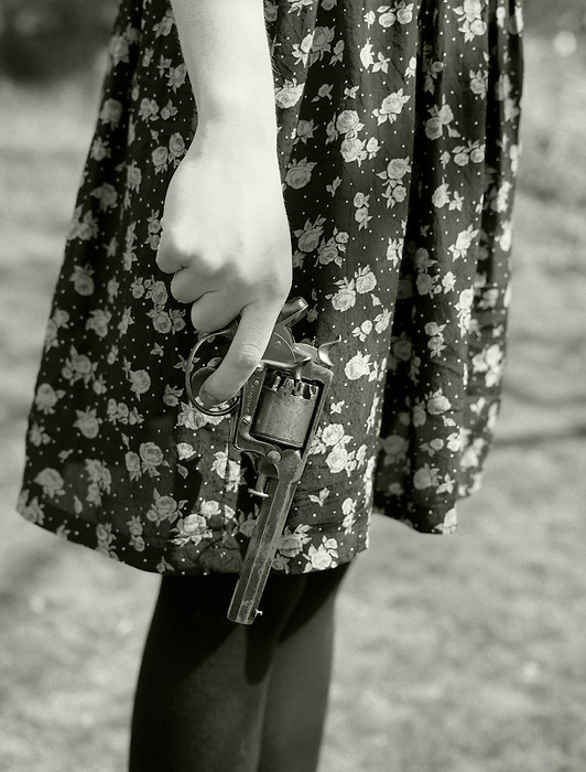 A young woman in a print dress holding an old-fashioned revolver<br />