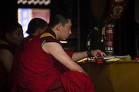 Des moines du Yonghegong pendant une récitation dans le grand hall d'assemblée.