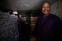 "Emanuel Nana, 51, a former frozen chicken importer, overlooks his interests in his frozen fish refrigerator cell, located in his fish store, part of his business complex an shopping center  in Cameroon's capital Yaounde on August 2007. When asked if he would go back to importing frozen chicken if the conditions allowed it her replied: "" Sure, it's a lot of money"".///..Cameroon's chicken industry is an example of  globalization strategies and free trade applied to developing countries..Legal imports of frozen chicken from the EU stopped around 2005 when the government of Cameroon raised import taxes on the good to a point where it became anti-economical for the exporters to ship  chicken to the country. .Several years of imports of tens of thousands of tons  of frozen chicken  destroyed the local chicken industry and represented in many cases, due to careless of hygienic conditions,  a serious threat for the consumer's health..Civil society groups, thanks to massive awareness campaigns and lobbying were able to turn the government in favor of preserving the countries' chicken industry, making of Cameroon a country to watch carefully in globalization affairs..Although such harmful imports were stopped many other goods that could be produced by the local economy are still flooding the country. European frozen chicken exporters simply  diverted their goods to other west  and central african countries."