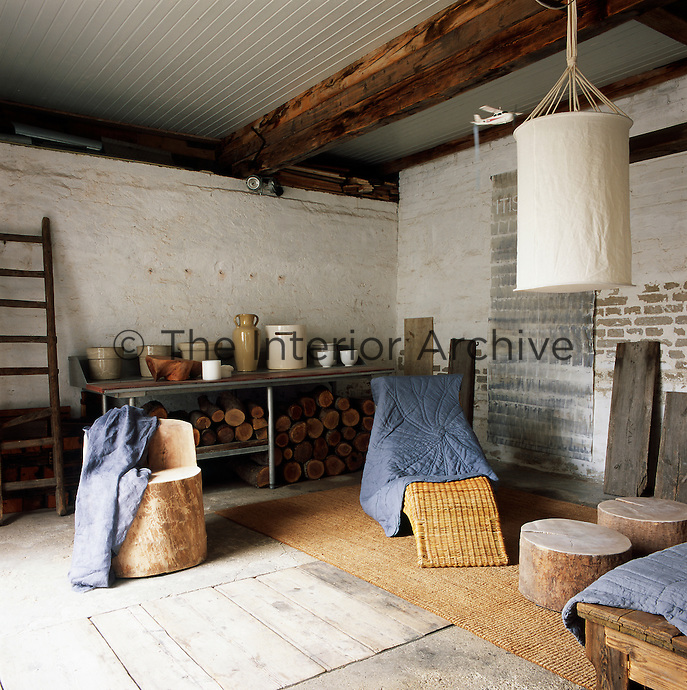 A wicker chair, a metal storage unit and sawn off tree trunks as a chair and tables is the basic furniture in a  room, which has a rustic, unfinished look with painted brick walls and bare floorboards