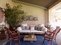 A large bamboo sofa piled with cushions and a pair of rattan armchairs creates a comfortable and welcoming seating area at one end of the covered terrace