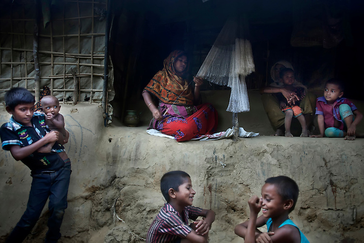 A woman repairs fishing net, as children play at a camp for Rohingya people in Ukhiya.
