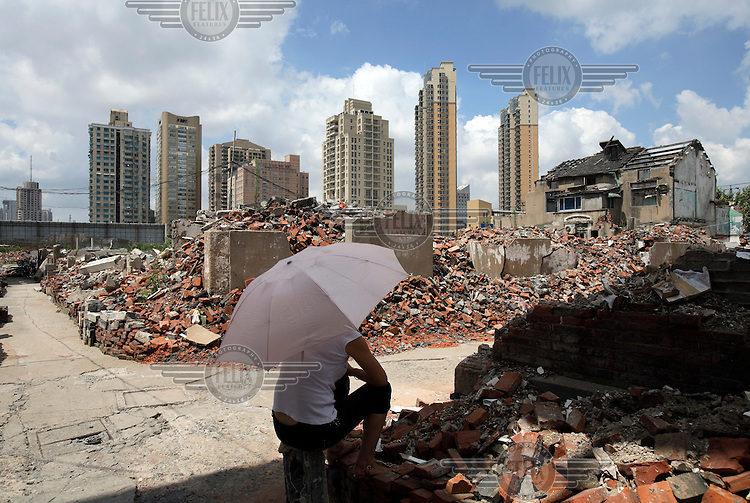 A woman sits under an umbrella waiting for people to buy her scrap and old furniture in an old neighbourhood in the process of being demolished to make way for new developments in Shanghai.