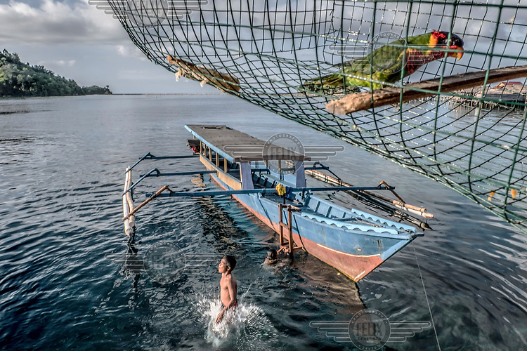 A Bajau child leaps from a boat into the water.