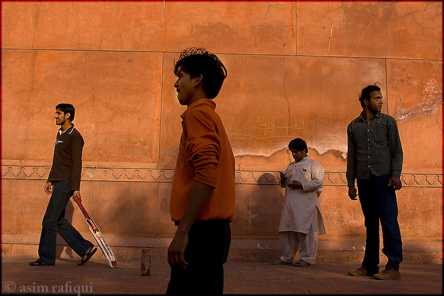 playing cricket, considered the national sport, along the walls of the grand badshahi mosque in the old city of lahore