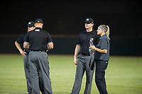 AZL Giants athletic trainer Charlene Wichman offers water to Minor League umpires Jeff Hamann, Pete Talkington, and Ray Patchen during a game against the AZL Cubs on September 5, 2017 at Scottsdale Stadium in Scottsdale, Arizona. AZL Cubs defeated the AZL Giants 10-4 to take a 1-0 lead in the Arizona League Championship Series. (Zachary Lucy/Four Seam Images)