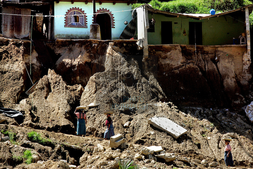 Mayan women walk on a path where two houses were destroyed and others damaged by landslides. Torrential rains associated with Hurricane Stan inundated parts of Central America in early October, causing flooding and mudslides across western Guatemala.<br />