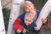 Smiling sister and brother playing in birch tree age 3 and 6.  St Paul  Minnesota USA