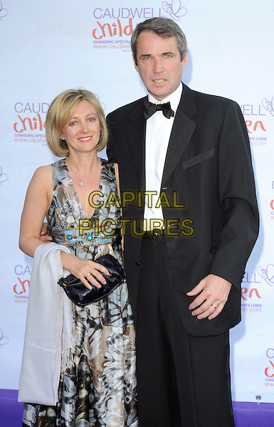 JANET & ALAN HANSEN.at the Caudwell Children Butterfly Ball at Battersea Evolution, London, England, UK, May 20th, 2010 .half length tuxedo grey gray pattern dress black bow tie tux tuxedo married wife husband couple clutch bag .CAP/BEL.©Tom Belcher/Capital Pictures.
