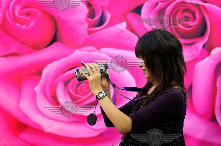 Young woman taking a photo in a gallery in 7-9-8 district. Also known as 'Dashanzi', this art zone consists of hundreds of galleries, studios and media businesses in former military factories in a Bauhaus-esque designed complex in the North West of the city.