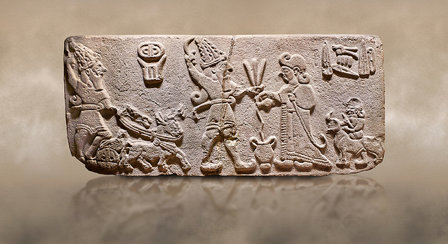 "Aslantepe Hittite Orthostat. Limestone, Aslantepe, Malatya, 1200-700 B.C. <br /> <br /> Scene of offering drink and sacrifice. The god, with a symbol of divinity above, is in the chariot while holding a boomerang in his hand and a sword at his waist. The same god holds a lightning bundle in the middle. On the right, the king offers a drink to god. The inscription above reads ""Great, powerful King Sulumeli"". A servant stands behind holding a bull for sacrifice to the gods. Anatolian Civilisations Museum, Ankara, Turkey.<br /> <br /> Against a brown art background."