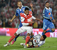 BOGOTÁ -COLOMBIA, 22-02-2014. Wilder Medina (C) de Independiente Santa Fe disputa el balón con Luis Delgado (Der) y Andres Cadavid (Izq) del Millonarios durante partido por la fecha 7 por la Liga Postobón  I 2014 jugado en el estadio Nemesio Camacho el Campín de la ciudad de Bogotá./ Independiente Santa Fe player Wilder Medina (C) fights for the ball with Millonarios player Andres Cadavid (L) and Luis Delgado (R) during match for the 7th date for the Postobon  League I 2014 played at Nemesio Camacho El Campin stadium in Bogotá city. Photo: VizzorImage/ Gabriel Aponte / Staff