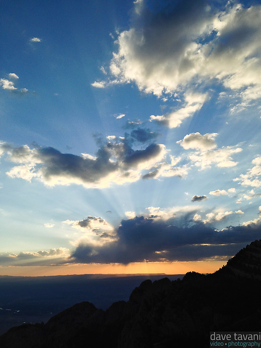 The sun dips behind a few clouds, as seen from Sandia Peak outside of Albuquerque, New Mexico.