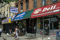 A group of buildings with retail on the first floor on a block in the Harlem neighborhood of New York on Sunday, June 23, 2013.  (© Frances M. Roberts)