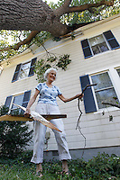 Sue Copeland cleans up debris from a large tree that fell onto her home from Friday's storm on St. George Avenue in Crozet, VA. Strong winds from the storm downed numerous trees and caused massive power outages across the area.