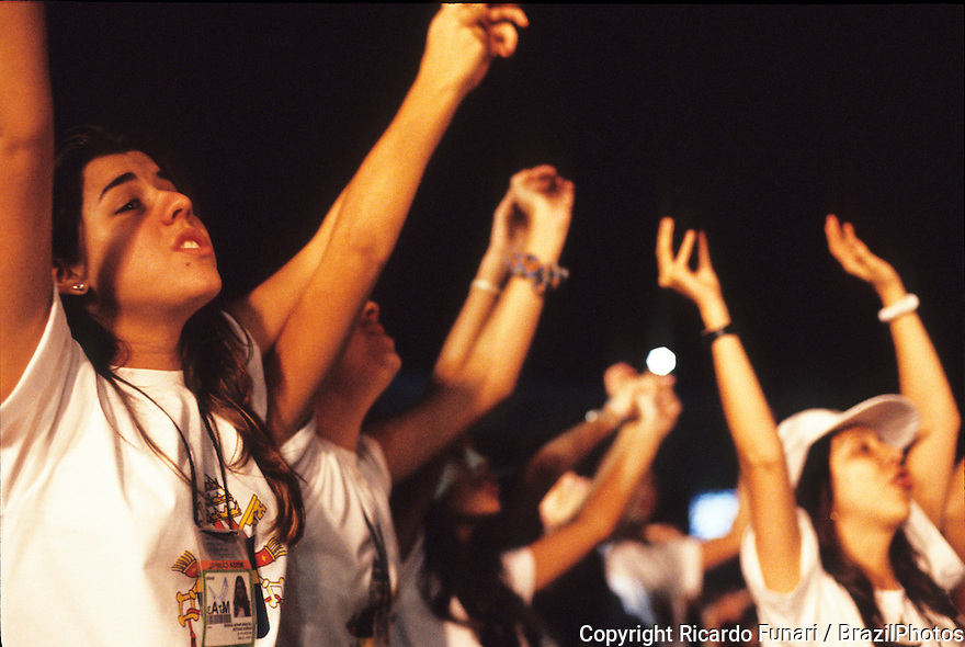 Latin America / Catholicism. Teenagers sing during religious ceremony. Visit of Pope Joao Paulo II to Brazil in 1997.
