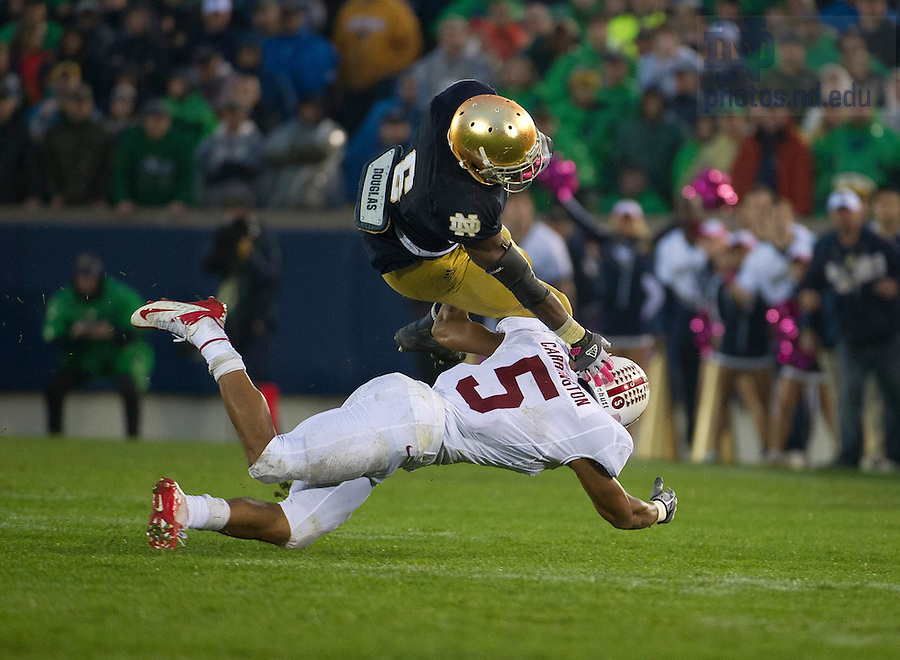 Oct. 13, 2012; Notre Dame running back Theo Riddick is tripped up by Stanford free safety Devon Carrington during the second half at Notre Dame Stadium. Photo by Barbara Johnston/University of Notre Dame