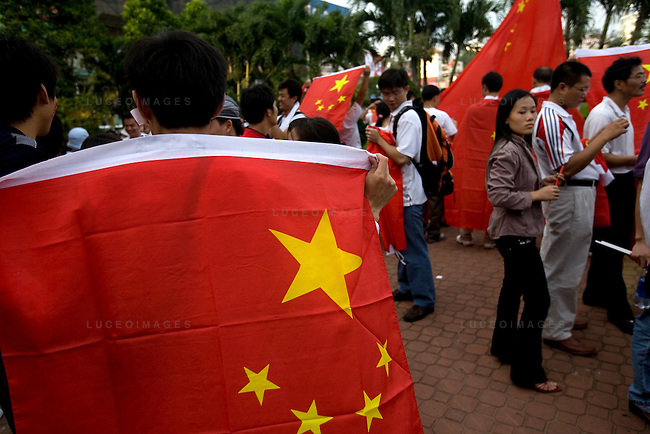 Pro-China demonstrators get ready in the city center as they wait for the Olympic torch relay to begin in downtown Ho Chi Minh City, Vietnam. Vietnamese officials ushered anyone holding a Chinese flag into a single area and then marched the people to the starting area of the relay...Thousands of people filled the streets of downtown District 1 in Ho Chi Minh City, Vietnam, to catch a glimpse of one of the 60 torchbearers complete the last leg of the Olympic flame's global journey outside China.  The Olympic torch relay began at the Opera House in the city center and conclude at a stadium near the Tan Son Nhat International Airport, covering a route of 10-13 kilometers. The Olympic flame will head to Hong Kong next. Photo taken Tuesday, April 29, 2008. Kevin German / kevin@kevingerman.com