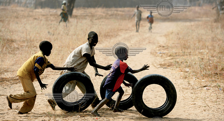Children play with old tyres..