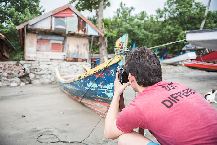 Photographer taking a photo of old fishing boats at Pulau Weh Island, Aceh Province, Sumatra, Indonesia