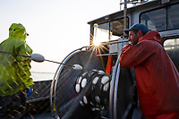 """Alistair Stewart from Vashon island, WA mans the hydraulic brakes while making a set on the F/V Mr. Fox in the Nushagak River in Bristol Bay in Alaska on July,8, 2019. Stewart, originally from Cambridge, England, has been fishing in Bristol Bay for seven years and uses the income to help pay his mortgage. """"It seems like a terrible decision they're about to make based on making a few people very rich,"""" he says about the Pebble Mine. (Photo by Karen Ducey)"""