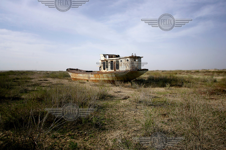 The remains of an abandoned trawler left to decay on what was once the Aral Sea's shore, now about 40 kms distant. During the 1950s and the 1960s the rivers that feed the Aral Sea (the Amu Darya and the Syr Darya) were diverted for irrigating cotton and other crops. This caused the lake to shrink uncovering sediments heavily polluted with industrial fertilizers that were washed into the lake over the preceding decades. Without the lake's water to contain it these toxic particles were spread by the wind and have caused numerous health problems in surrounding communities. Furthermore, as the lake evaporated the remaining water became increasingly saline and unable to sustain life, destroying the fishing industry. Muynak, once a thriving fishing port, became a depressed and dusty town far from the receding shore.