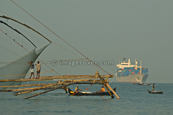 Indian fishermen working their old fashioned chinese style fishing nets in Fort Cochin (Fort Kochi), Cochin, Kerala 2005. In contrast a modern container ship is passing by.