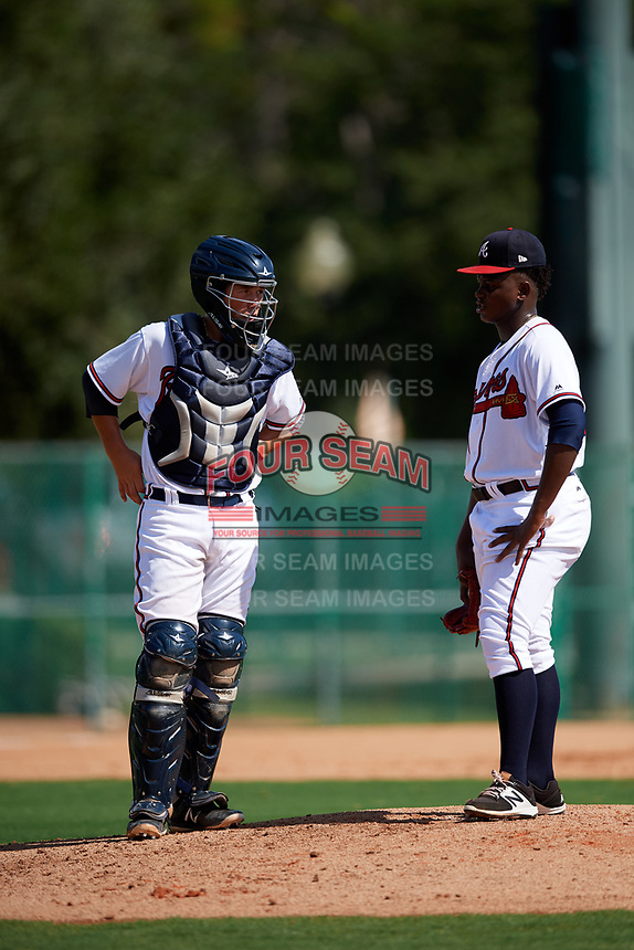 GCL Braves starting pitcher Luis De Jesus (23) talks with catcher Logan Brown (28) during the first game of a doubleheader against the GCL Yankees West on July 30, 2018 at Champion Stadium in Kissimmee, Florida.  GCL Yankees West defeated GCL Braves 7-5.  (Mike Janes/Four Seam Images)