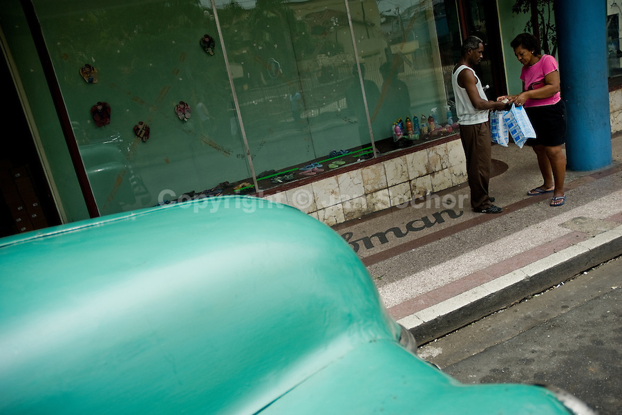 A Cuban couple switch plastic bags in front of an empty shop window in the centre of Santiago de Cuba, Cuba, 29 July 2008. About 50 years after the national rebellion, led by Fidel Castro, and adopting the communist ideology shortly after the victory, the Caribbean island of Cuba is the only country in Americas having the communist political system. Although the Cuban state-controlled economy has never been developed enough to allow Cubans living in social conditions similar to the US or to Europe, mostly middle-age and older Cubans still support the Castro Brothers' regime and the idea of the Cuban Revolution. Since the 1990s Cuba struggles with chronic economic crisis and mainly young Cubans call for the economic changes.