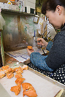 Using an airbrush to paint plastic deep fried chicken at Maiduru Corporation, Tokyo, Japan, 22nd December 2008. Maiduru corporation makes highly realistic plastic food for display in restaurant and cafe windows. .