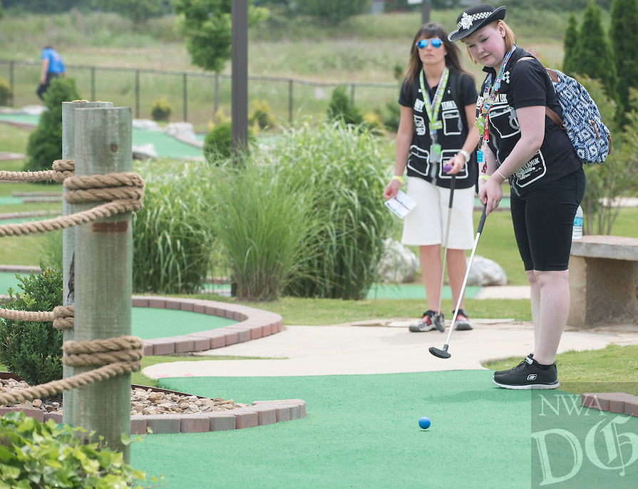 NWA Democrat-Gazette/J.T. WAMPLER  Zara Barker (CQ) makes a putt Tuesday May 31, 2016 while playing with Aimee Gartland(CQ), both of the United Kingdom, at Golf Mountain miniature golf in Lowell. Around 200 team members from Asda, a UK based grocery store chain, are attending the annual Wal-Mart shareholders meeting in Fayetteville this week.
