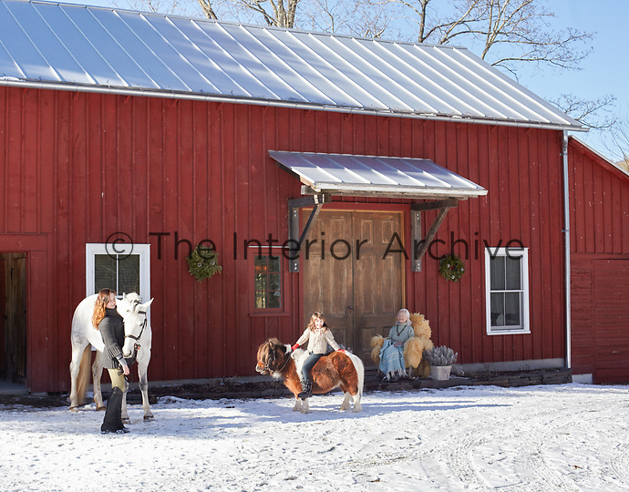Ponies and family members in the snow outside the red-painted clapboard barn