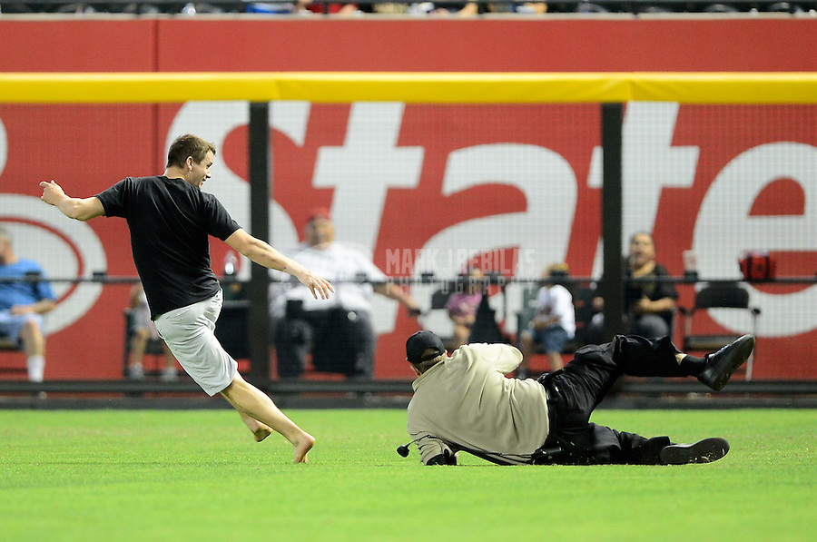 Apr. 25, 2012; Phoenix, AZ, USA; A security guard (right) falls as he chases a fan on the field between innings of the game between the Arizona Diamondbacks against the Philadelphia Phillies at Chase Field. Mandatory Credit: Mark J. Rebilas-