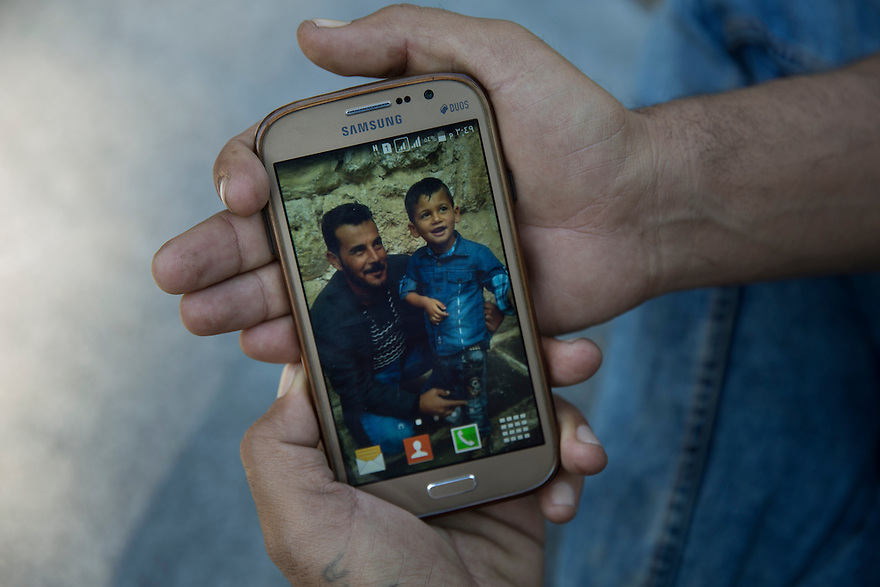Yassir Bashar holds a cell phone photo of him with his son, who was kidnapped by ISIS.  When ISIS swept through his village, they captured his wife Khaida and killed one of his two sons, along with two of Yassir's brothers. After a year in captivity, his younger son,  Sezar, 5, was released and brought to Germany with his sister and her husband. Yassir arrived in Greece last month to find the border closed. He has heard only once from his wife, who is imprisoned in Raqqa, Syria. She wrote him a letter that was carried to him by a hostage released by ISIS. Yassir recently moved from Idomeni camp to Petra, a camp exclusively for Yazidis, who say they were fearful living among so many Muslims. He is trying desperately to reunite with his son and sister in Germany.