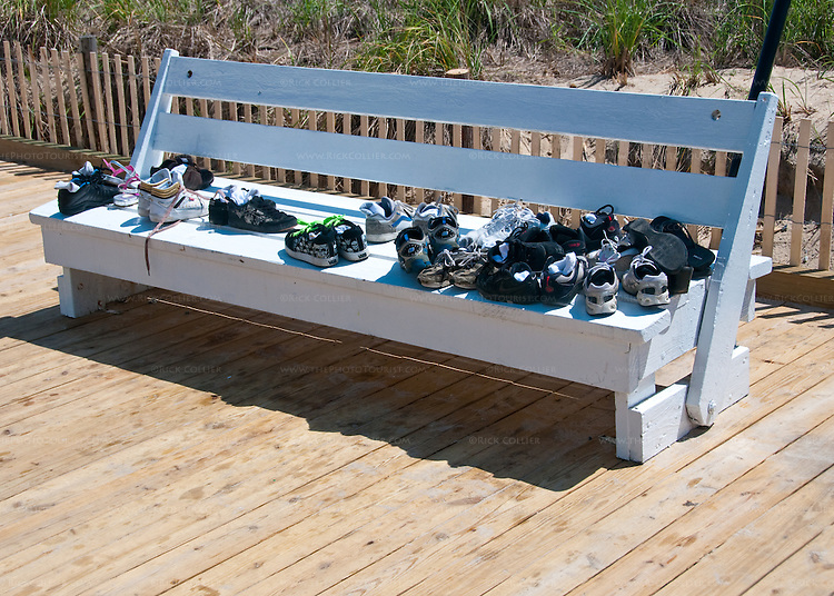 A group of kids has piled their shoes on a bench so they could go walk on the beach on one of the first warm days at Rehoboth Beach, Delaware, USA.