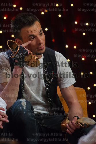 Dancer Robert Marko talks with the dancing shoes of his partner singer Gabi Toth in his hands in the live broadcast celebrity dancing talent show Saturday Night Fever by Hungarian television company RTL II in Budapest, Hungary on March 16, 2013. ATTILA VOLGYI