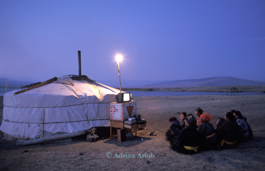 A Tsaatan herdspeople watch a video powered by a motorcycle,  on Tsaatan Uul lake,   Outer Mongolia.