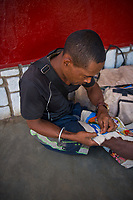 Africa, Madagascar, Ambositra city. Man doing sewing.