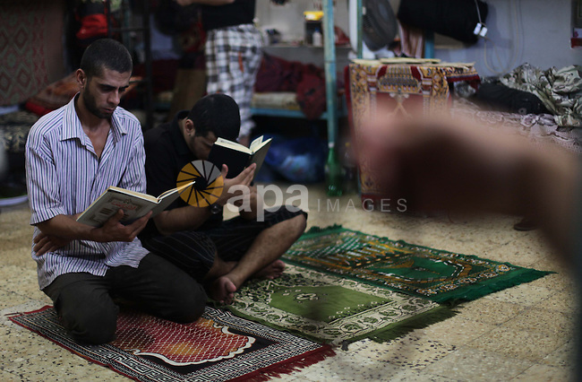 Palestinian inmates read holy Quran during the holy month of Ramadan at prison controlled by the Palestinian police in Gaza city on 28 July 2013. Palestinian police released more than 65 criminal inmates before the fasting month of Ramadan. Photo by Ashraf Amra