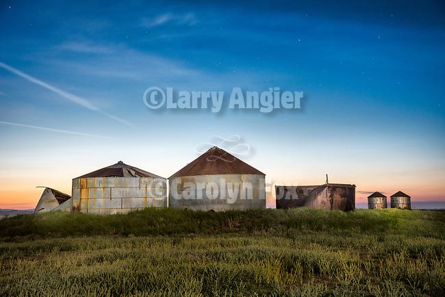 Abandoned grain storage tanks at dusk, R C Ranch, Carrizo Plain, San Luis Obispo County, Calif.