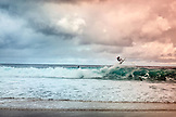 USA, Oahu, Hawaii, a young woman surfer gets some air at Pipeline Beach on the North Shore