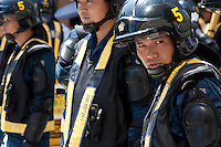 Policemen in riot gear line up and keep watch at a road block near Yasukuni Shrine. On August 15th every year people gather at Yasukuni Shrine to commemorate the end of the Pacific War. Notionally a call for remembrance and continued peace it is also a Mecca for right wing nationalist including  the paramilitary Uyoku Dantai. Tokyo, Japan, August 15th 2009