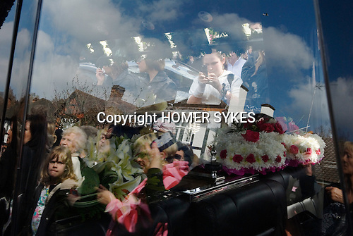Jade Goody Funeral April 4 2009. TV Reality Star funeral service well wishers gather outside St Johns Chuch Buckhurst Hill Essex England. Young girl uses her mobile phone to take a picture of floral tributes. Reflections in herast car windows.