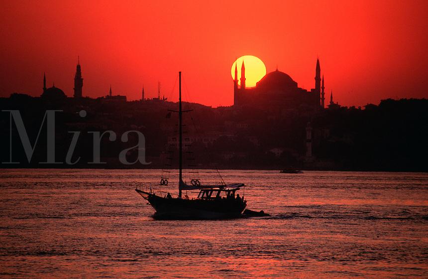 Dramatic view of a crimson sunset over the Aya Sofya (Hagia Sophia) across the Bosphorus strait. Istanbul, Turkey.