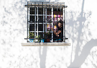 Annuska at her smoking corner as seen from the street.  Fourth move in six months after the September 19 2017 earthquake. From Roma Norte to the Edificios Condesa, Mexico City, Mexico