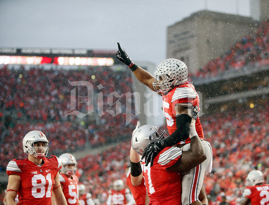 Ohio State Buckeyes running back Ezekiel Elliott (15) celebrates his touchdown with Ohio State Buckeyes offensive lineman Chase Farris (57) against Michigan State Spartans in the 1st half of their game at Ohio Stadium on November 21, 2015.  (Dispatch photo by Kyle Robertson)